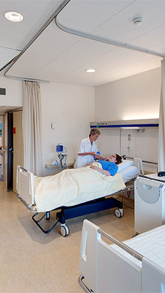 A nurse checks on her patient in a UMCG patient room, lit using Philips' energy saving lighting